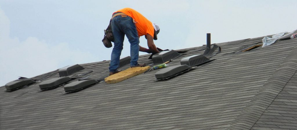 A professional working on roofing repairs